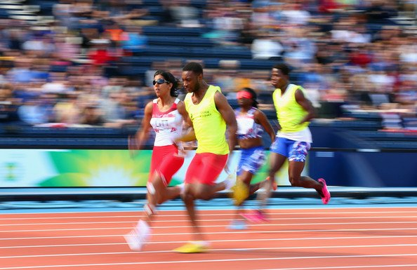 A picture of Selina Litt sprinting with a guide runner in the Glasgow 2014 Commonwealth Games.