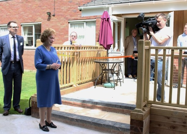 A picture of the Dowager Duchess cutting an orange ribbon in front of the Butterfly Lounge.