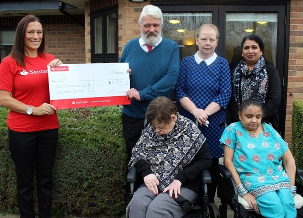 A picture of a Santander employee, the Residential Manager and residents with the cheque.