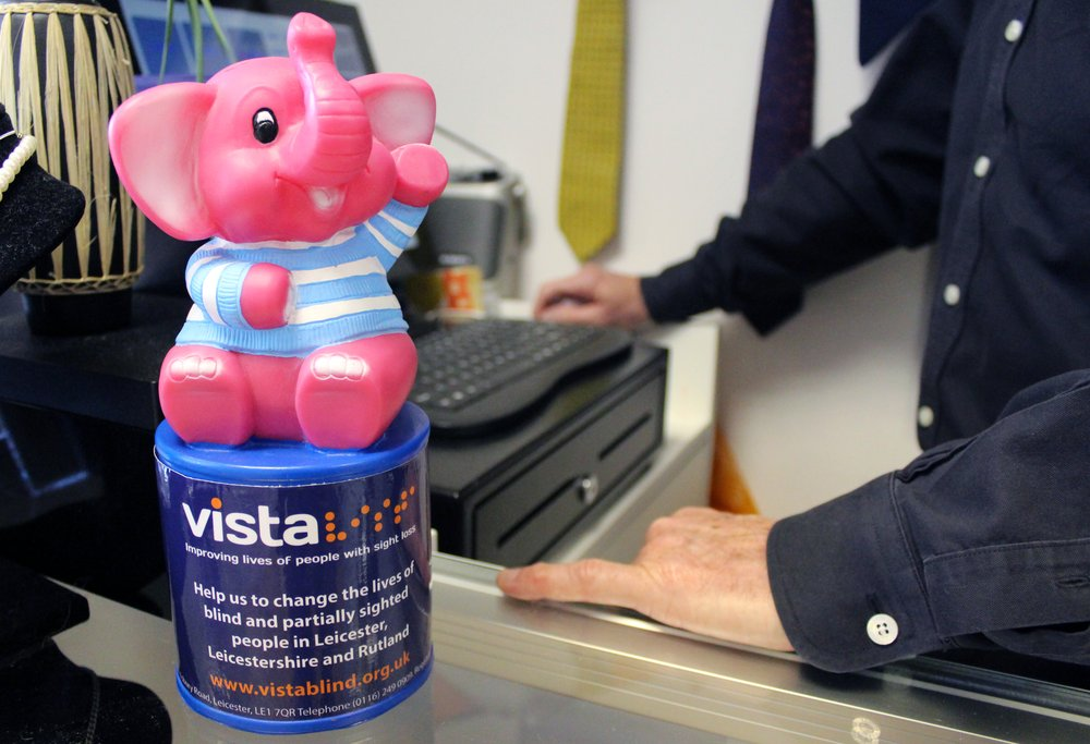 A picture of a Vista pink elephant collection box on a shop counter.