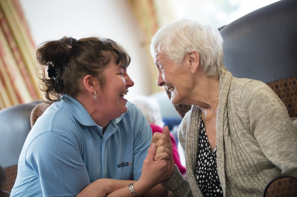 A picture of a Vista care assistant holding hands and smiling with a resident.