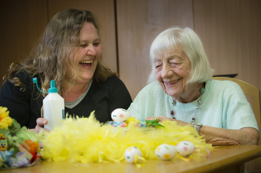 A picture of a care assistant and resident taking part in an activity