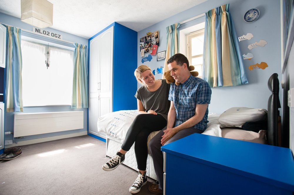 A picture of a staff member talking to a resident in his bedroom.