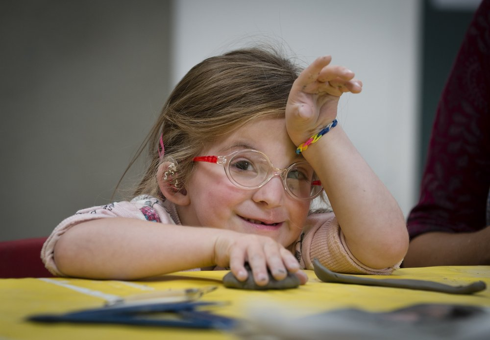 A picture of little girl wearing glasses, taking part in a children's craft activity.
