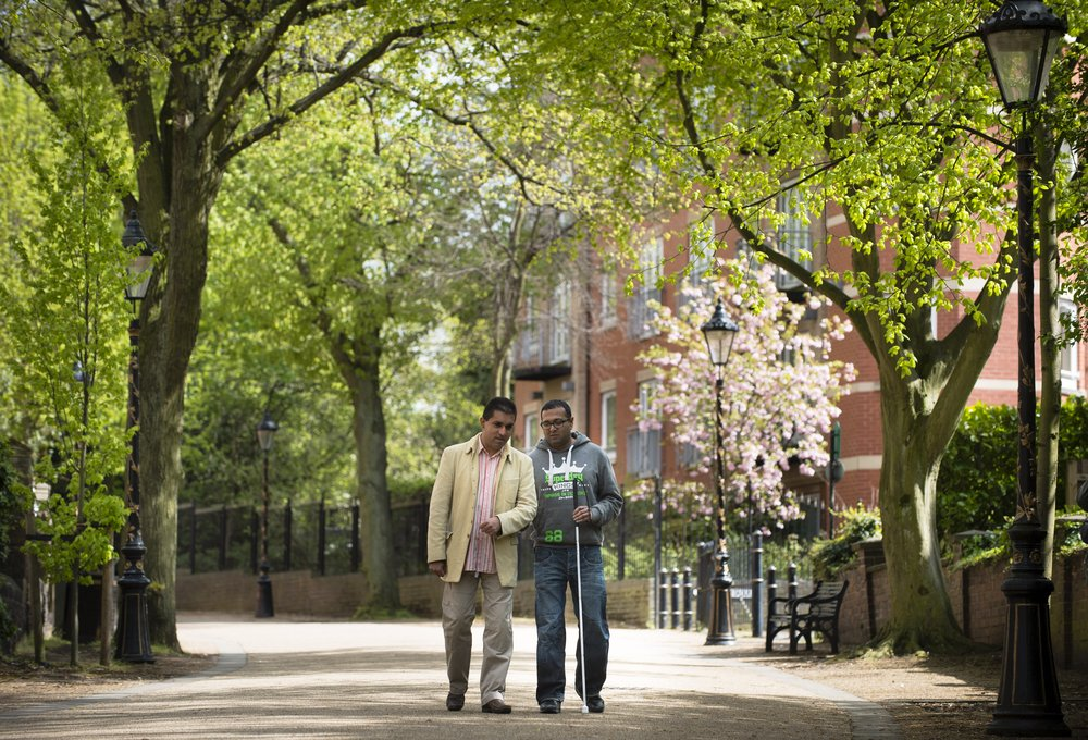 A picture of two males, one with a cane, walking together along New Walk in Leicester.