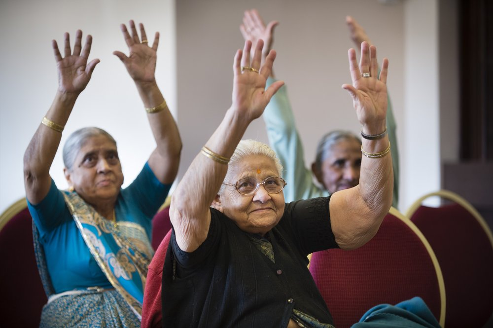 A picture of three elderly ladies taking part in a seated exercise session.