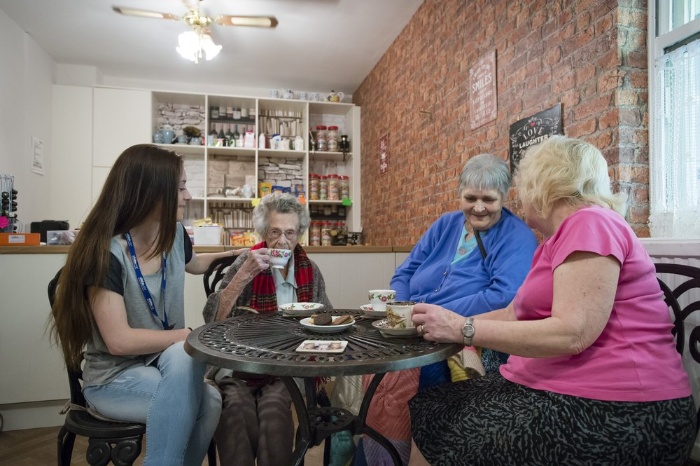 A picture of a staff member sat with residents in the home's cafe.