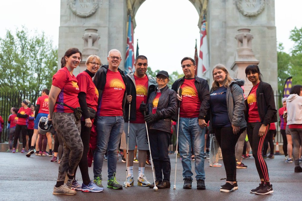 Group shot of 8 Vista runners, wearing Red Sunrise City t-shirts, standing in front of the war memorial in Victoria Park