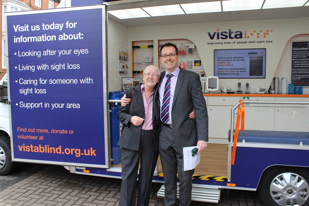 A picture of Chief Executive Paul Bott with a service user in front of Vista's vehicle.