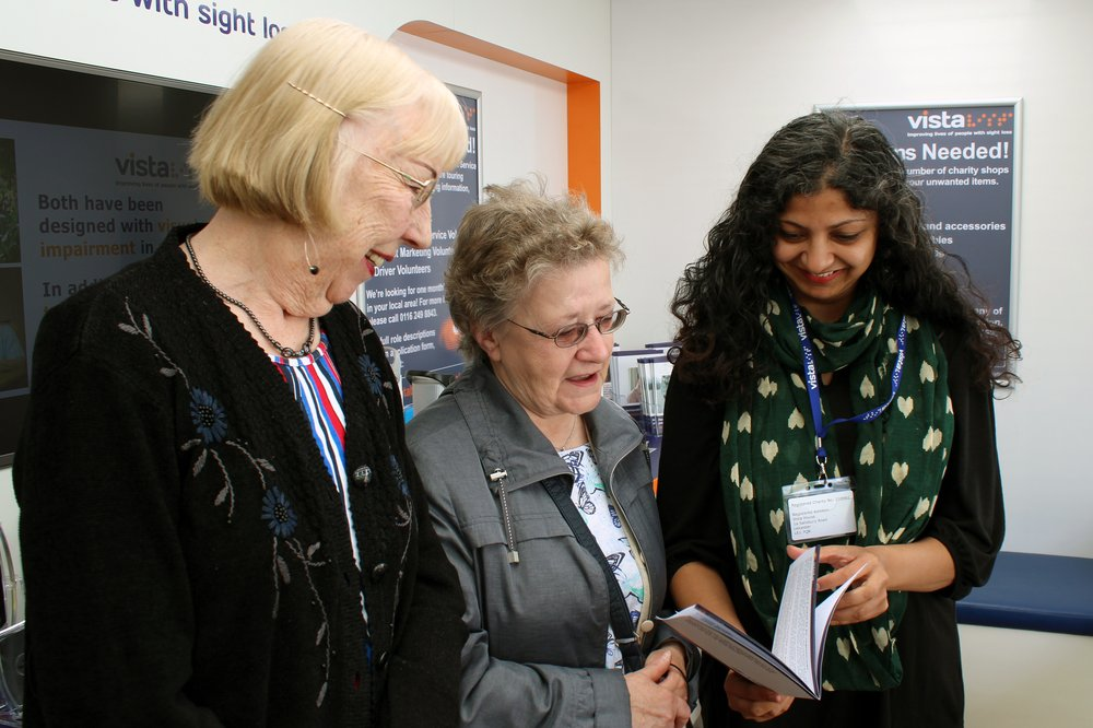 A picture of a Vista volunteer providing information to two ladies.