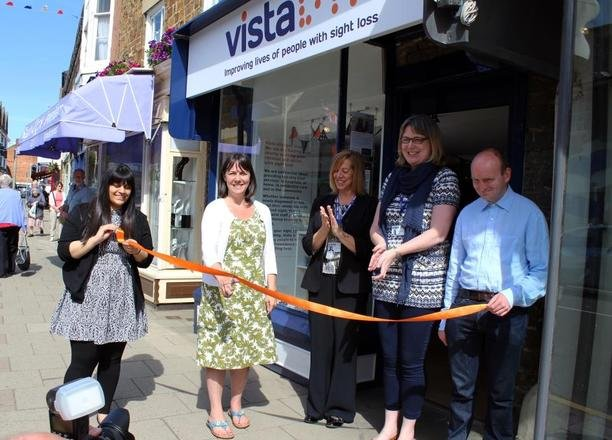 A picture of an orange ribbon being cut in front of the charity shop doors.