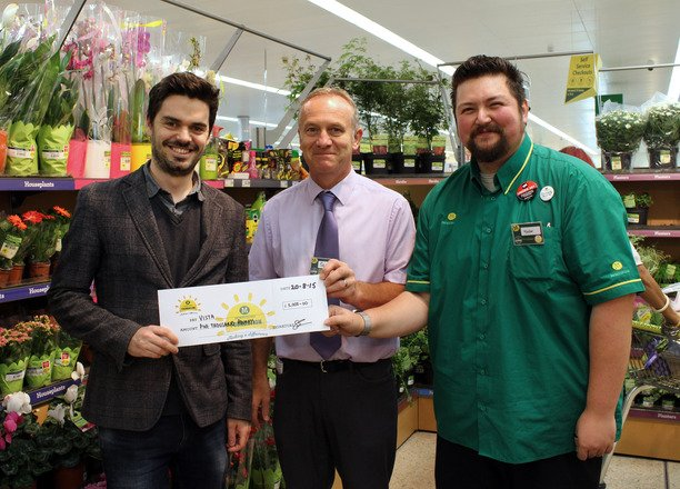 A picture of Chris Anderson and two Morrisons employees holding the cheque.