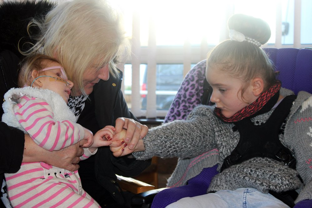 A picture of a two young girls holding hands in a music therapy session.