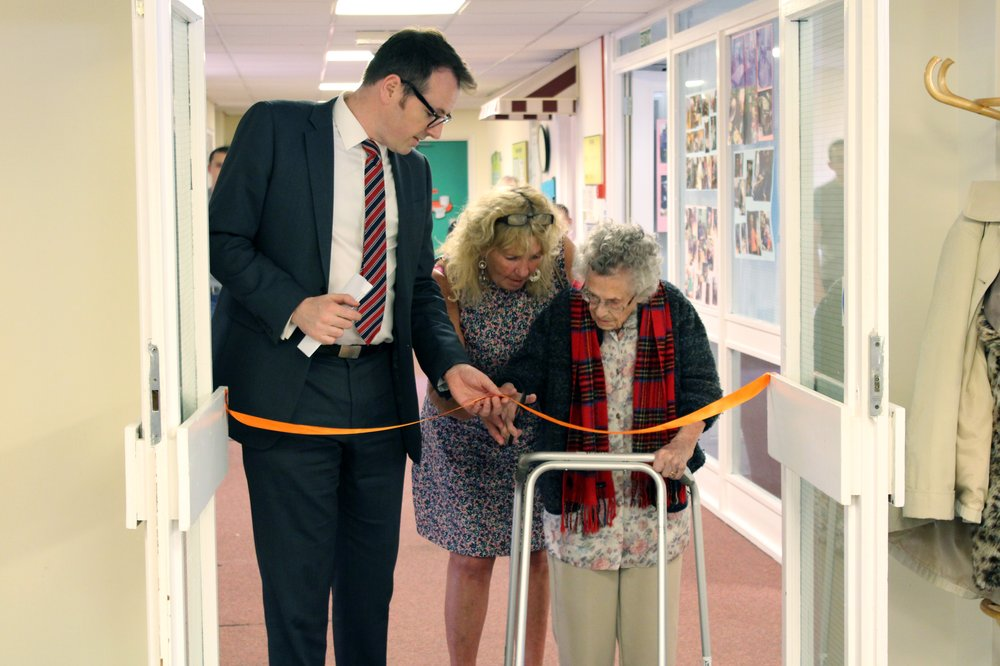 A picture of Paul Bott and Julie Rudd with a resident cutting the ribbon