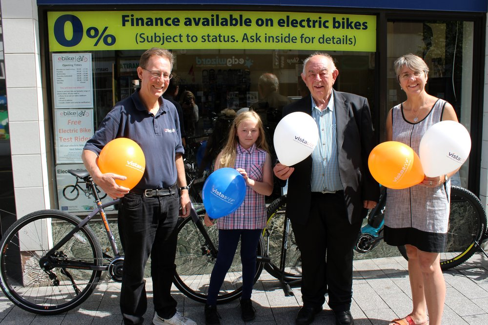 A picture of Liam, his dad Henry, granddaughter Rosie and Vista Fundraiser Louise outside the bike shop.
