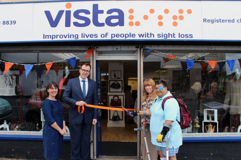 A picture of Vista staff and a service user cutting the ribbon to open the charity shop.