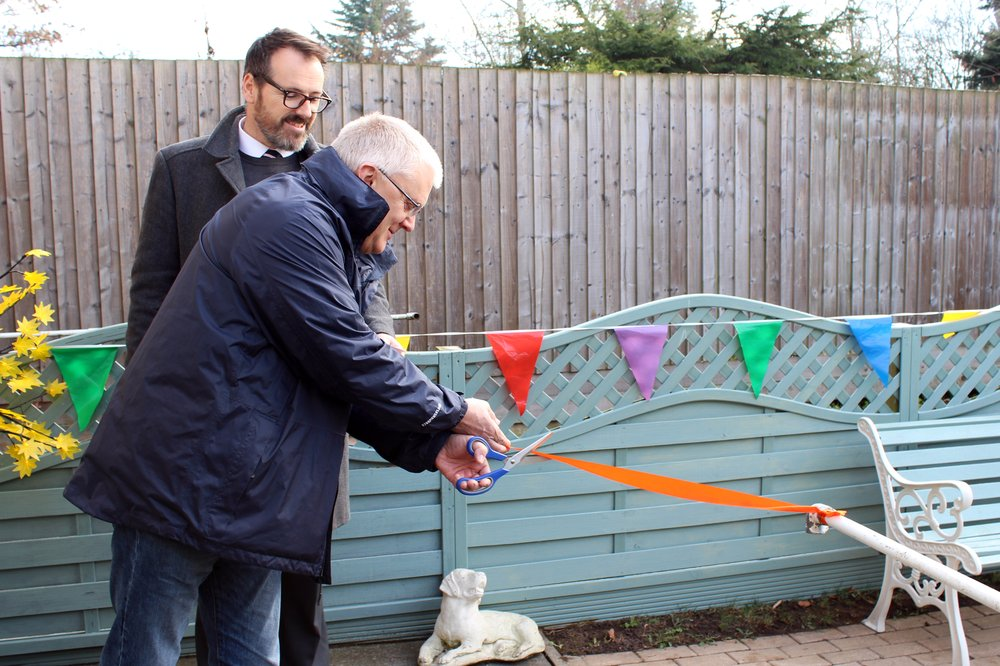 A picture of Chris Arrowsmith from Global Payments cutting the ribbon to open the sensory garden.
