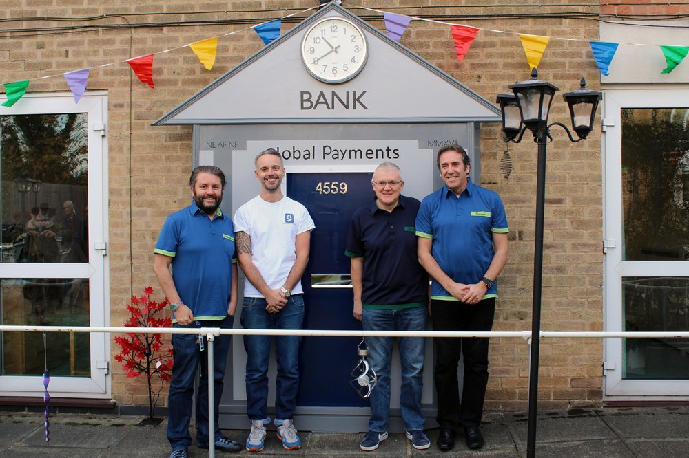 A picture of the Global Payments team in front of the mock bank in the sensory garden.