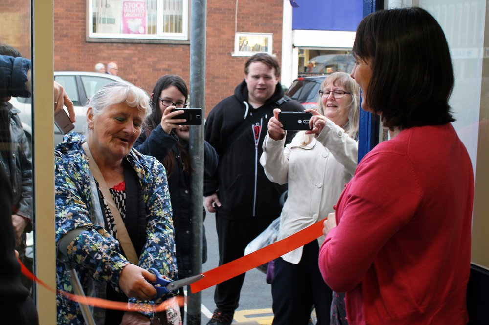 A picture of a lady cutting the ribbon to open the Wigston charity shop.
