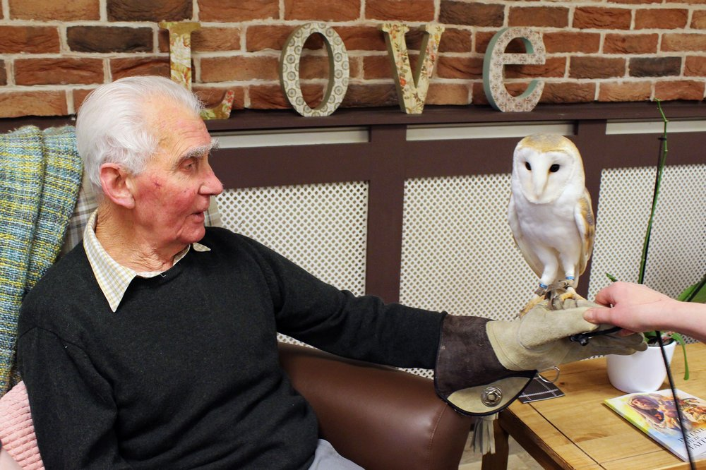 A picture of a resident holding an owl on his hand.