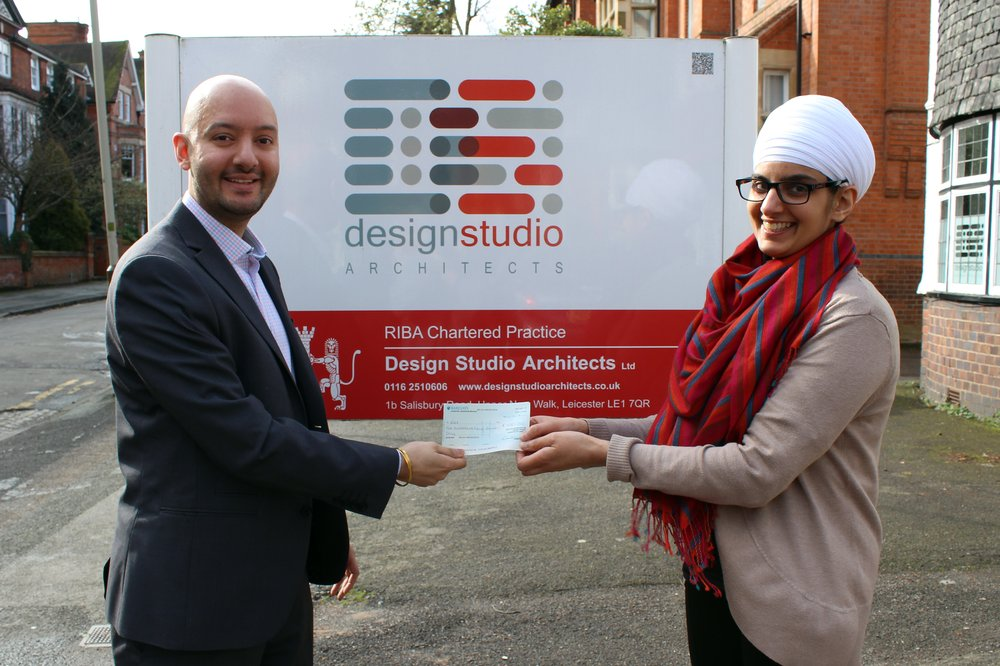A photo of Design Studio Architect's Managing Director presenting a cheque to Vista.