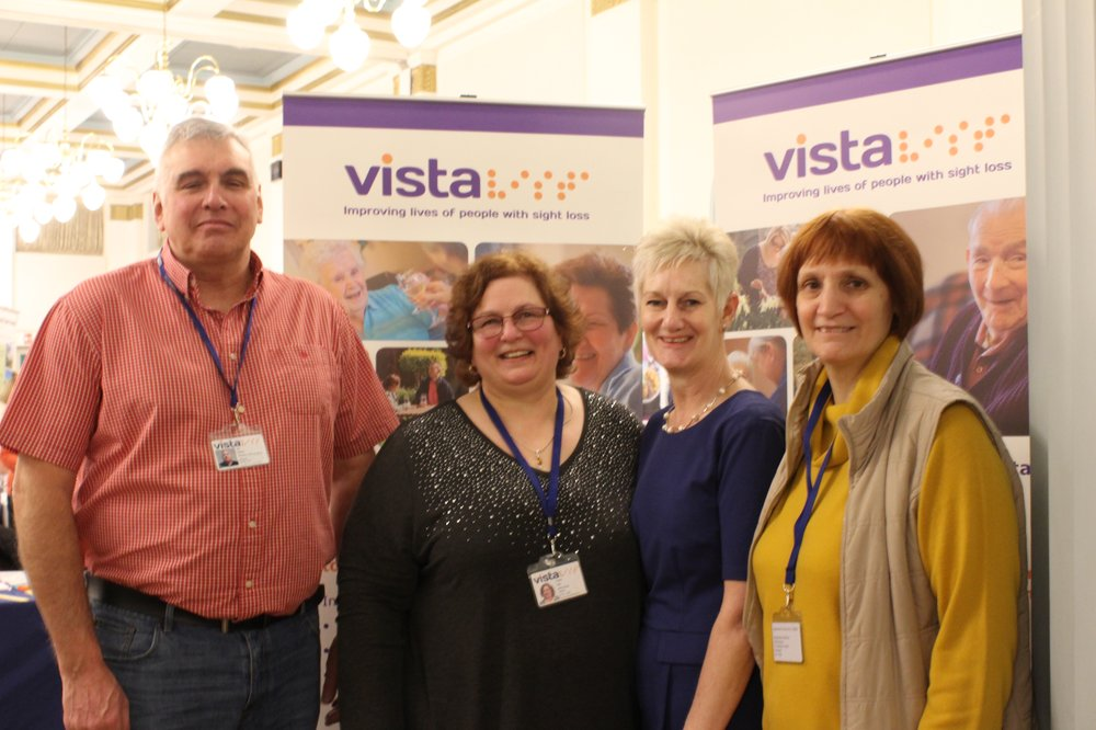 A picture of the befriending team in front of Vista pop-up banners.