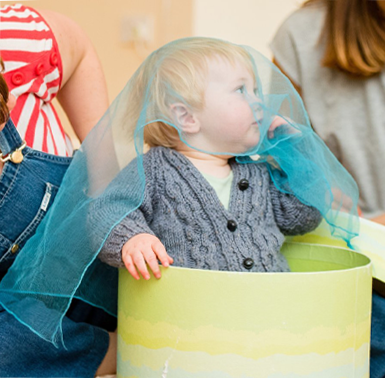 A picture of little child with blue fabric over their head, sat in a bucket