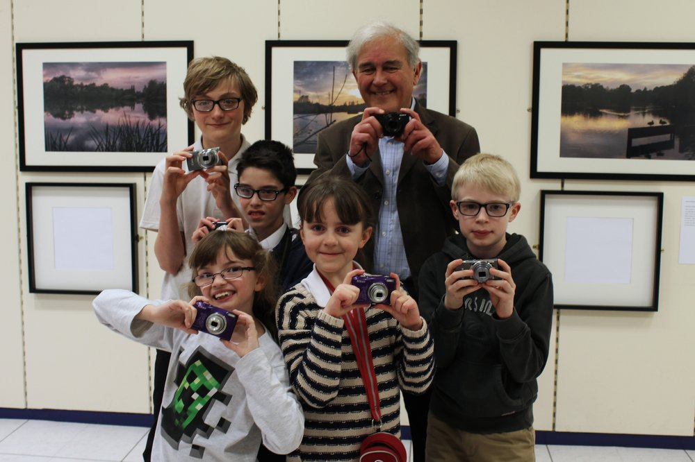 A picture of Vista Ambassador Brian Negus with children and young people, all holding cameras.