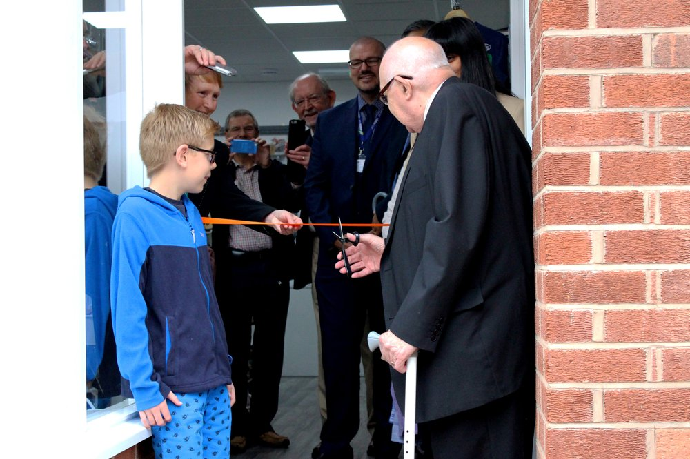 A picture of a young boy and an older gentleman, supported by Vista, stood in front of the new Rothley shop.