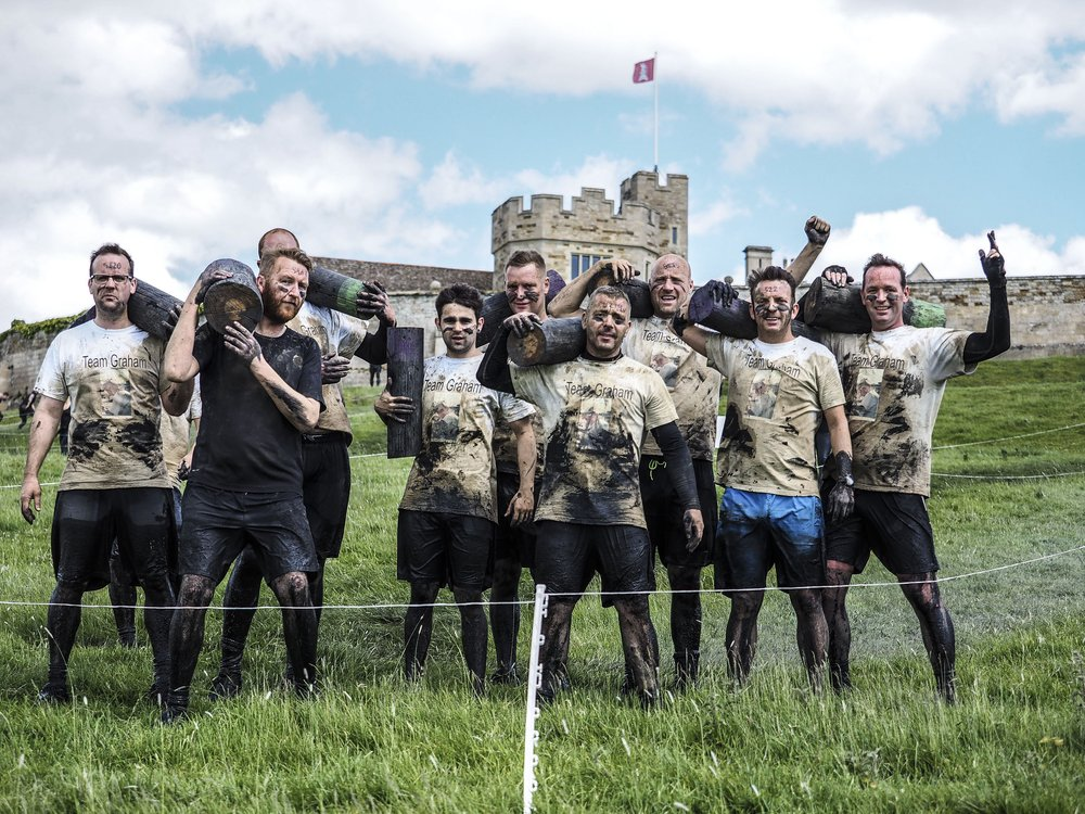A picture of a group who have taken part in the race, covered in mud and cheering.