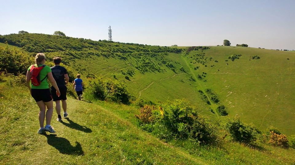 A picture of people running over the scenic South Downs hills.