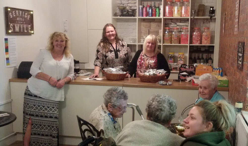 A picture of staff and residents at the new sweet shop.