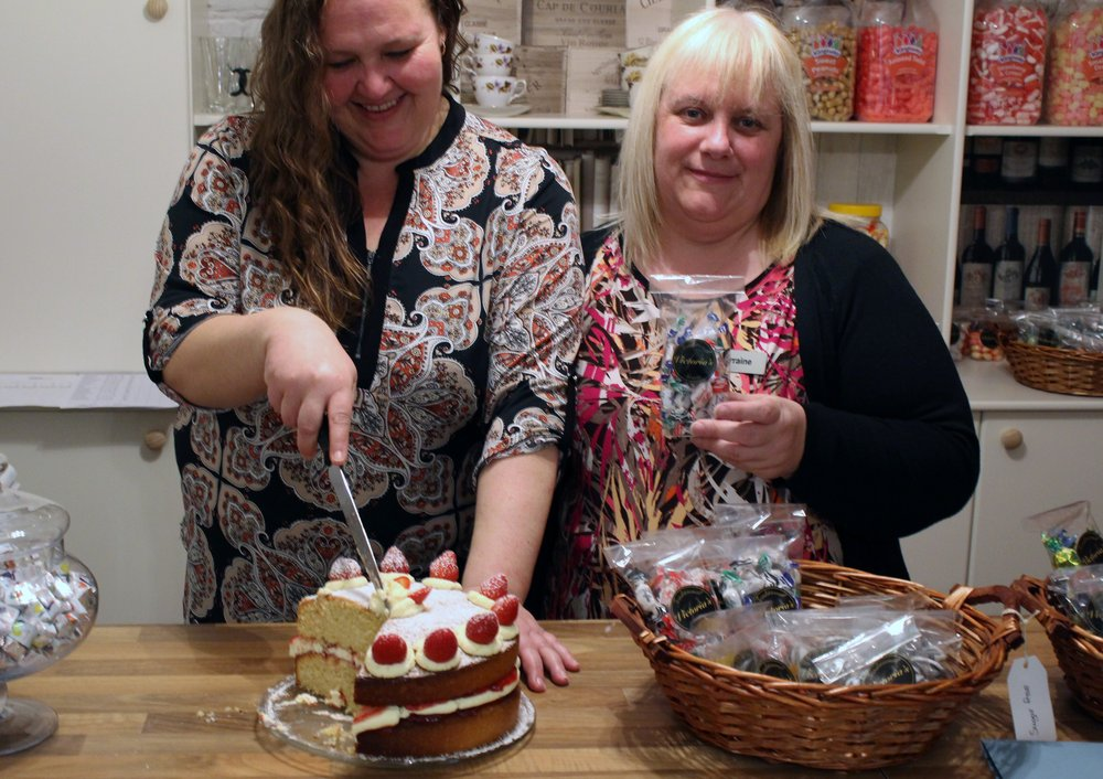 A picture of two care staff stood at the sweet shop counter, cutting a slice of cake.