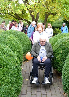 An elder man in a wheelchair being pushed by a smiling carer through gardens