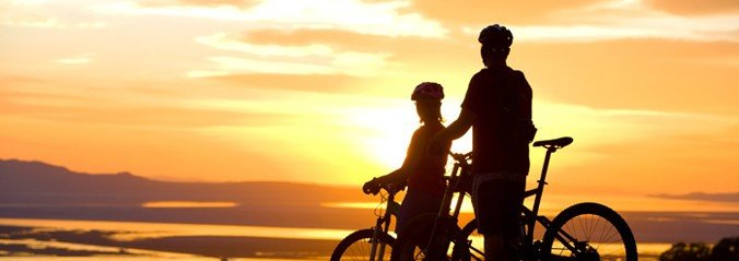 A picture of two cyclists with the sunset behind them.