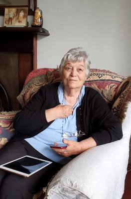 Imelda is sitting in an arm chair, wearing a blue shirt and black cardigan, an iPad rests of her lap.