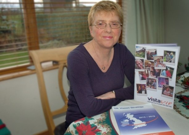 A picture of Jenny Pearce sat at a table with Vista and UK Vision Strategy literature.