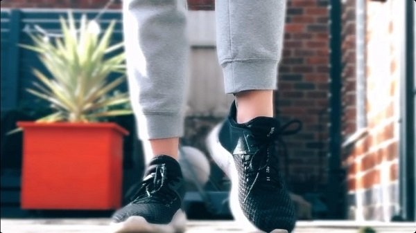 Image is of a close-up of someone taking a step and wearing trainers.