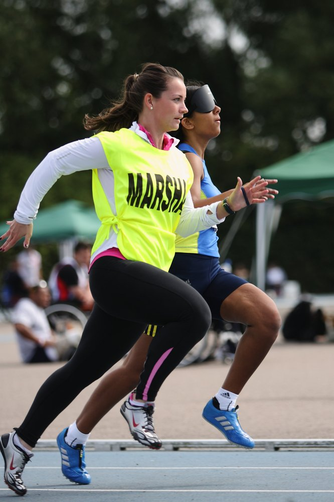 A portrait picture of Selina Litt running next to a guide runner.